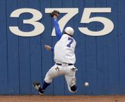 A DEEP FLY BALL GOES OVER THE OUTSTRETCHED GLOVE OF KANSAS UNIVERSITY OUTFIELDER BROCK SIMPSON in the third inning of KU's game against Texas. The Longhorns earned an 11-6 victory Thursday at Hoglund Ballpark in the opener of a three-game series.