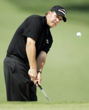 Phil Mickelson chips to the seventh green during the first round of the Masters. Mickelson, the defending champion, shot a 4-over-par 76 on Thursday in Augusta, Ga., that left him seven shots out of the lead.