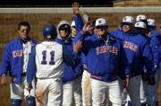 Ryne Price (11) is congratulated by his Kansas University teammates after he scored a fourth-inning run against Texas. KU scored six runs in the fourth in an eventual 14-6 victory over the seventh-ranked Longhorns on Friday at Hoglund Ballpark.