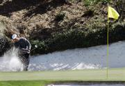Tiger Woods hits from a bunker on the 12th hole. Woods shot a third-round 72 at the Masters on Saturday in Augusta, Ga.