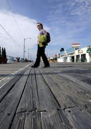"Georgina Shanley, an environmentalist, walks across the worn planks of the boardwalk in Ocean City, N.J. The town sought $1.2 million worth of Brazilian wood certified as having been harvested responsibly, to repair the boardwalk. ""Every second, 1.5 acres of rain forest is lost, and with it, thousands of plants and animals and habitat for the humans living there,"" Shanley said."