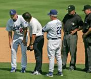 Los Angeles Dodgers pitcher Jason Schmidt, left, attempts to stretch his right hamstring after injuring it while covering first on a grounder. Schmidt left the game, which was won by Colorado, 6-3, Monday in Los Angeles.