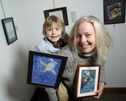 "Sara Stalling and her son Maya Spitzer, 6, are part of an art exhibit at the Lawrence Public Library gallery that includes artwork they have done together and individually. Maya holds a piece that he and his mother worked on together called ""There is a Bird in the Sky""; Stallings holds a mixed-media piece of hers titled ""Tsunami."""