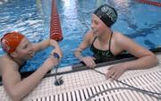 LAWRENCE HIGH'S ELLE WEBER, LEFT, AND FREE STATE'S MORGAN FLANNIGAN discuss their race at the conclusion of the 200-yard individual medley. Flannigan won the event Tuesday in a four-team meet at the Lawrence Indoor Aquatic Center. Weber took second.