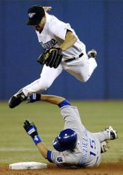 Toronto Blue Jays shortstop Jason Smith, top, jumps to avoid Kansas City Royals' Mark Grudzielanek. Grudzielanek was safe at second in the Royals' 6-3 victory Tuesday in Toronto.
