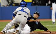 Kansas City catcher Jason Larue, left, tags out Toronto&#39;s Troy Glaus. The Blue Jays defeated the Royals, 7-4, on Wednesday night in Toronto.