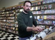Clark Morton, of Lawrence, flips through his inventory of newly arrived music at the CD Tradepost, 4000 W. Sixth St., one of the Morton family businesses. Clark's father, Jerry, said that because they sell a lot of used CDs, the digital download trend doesn't hurt their bottom line as it might for retailers who sell new music.
