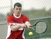 Lawrence High senior Travis Gage returns a volley. The Lions tied Olathe South, 6-6, Wednesday at the Lawrence Tennis Center.