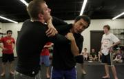 Mike Wisler, of Lawrence, tries to maintain his grasp around the neck of Muay Thai instructor Paul Sooksendao, Olathe, during class at Integrated Martial Science, 19th Street and Haskell Avenue. The academy offers Muay Thai kickboxing, Brazilian Jiu-Jitsu, mixed martial arts and other techniques.