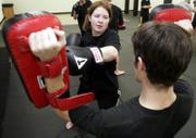 Kristin Colahan-Sederstrom, Lawrence, moves through a routine at Integrated Martial Science, a training academy of mixed martial arts styles.