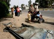 An Iraqi family walks past a car part after a car bomb exploded near Baghdad University. A troop surge intended to quell violence in the Iraqi capital has stretched the U.S. Army thin, and on Wednesday it was announced that troops would have to spend an additional three monts in Iraq.