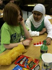 Clague Middle School students Jessa Gargan, left, and Zahra Al-hasnawy look over props used in a health program in their classroom in Ann Arbor, Mich. Healthy Schools, a collaborative program between Ann Arbor public schools and the University of Michigan Health System, teaches basic nutrition information and encourages physical exercise.