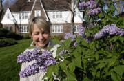 Linda Lungstrum views one of several lilacs outside her Tudor-style home near the Kansas University campus. She and her husband John like to travel, so she has filled her yard with low-maintenance plants.