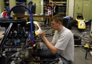 Kansas University senior Jon Miller, Overland Park, wrenches on the body of a Formula SAE car built and designed by engineering students, Thursday in Learned Hall. Many of the students involved with the project spent the day preparing the car for show Thursday night at Abe & Jake's Landing, 8 E. Sixth St. The 2006 model car is at back right.