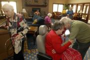 As Mae Bugert leaves the room, Beverly Edwards and Marion Howie greet each other with a hug in the activities room at Pioneer Ridge Retirement Community, 4851 Harvard Road. Remaining active throughout life is one way seniors can ward off depression.