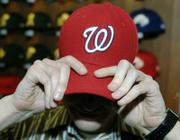 A New Era Cap Co. employee, Mike Wozniak, models a 59 FIFTY Authentic Collection On Field Cap with the Washington Nationals logo at the company's headquarters in Buffalo, N.Y. The new MLB caps are made of a polysynthetic fabric to aid in wick management for the players.