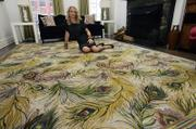 Fashion designer Nanette Lepore poses on a peacock-themed carpet in the living room of her home in New York's Greenwich Village. Lepore has joined a growing list of fashion designers - Calvin Klein and Liz Claiborne (with Nourison), Oscar de la Renta (with elson & co.), Vivienne Westwood, Paul Smith, Diane Von Furstenberg, Lulu Guinness (with The RUG Company) - all translating their passion for fashion design to floor coverings.