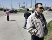 Martin Rosas, secretary-treasurer for United Food and Commercial Workers union, talks with a reporter while members of the UFCW union hand out fliers this month outside National Beef in Dodge City. Illegal immigrants are preparing for their possible arrest by saving money to pay for bail and bonds and drawing up documents for the care of their children.