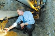 Jim Modig, Kansas University director of design and construction management, displays a handful of crumbling concrete and rusted steel in the underground tunnels below the university's power plant during a tour in September 2006. Modig said the repair to the tunnels was the highest priority for the university, with an estimated price tag of $8 million.