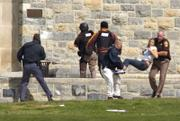 An injured woman is carried out of Norris Hall at Virginia Tech in Blacksburg, Va. A gunman opened fire in a dorm and classroom Monday at Virginia Tech on Monday, killing 32 people before he apparently killed himself, police said.