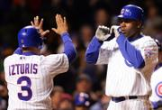 Chicago Cubs' Cliff Floyd, right, celebrates with teammate Cesar Izturis after hitting a three-run home run during the fifth inning against the San Diego Padres. The Cubs won, 12-5, Monday in Chicago.