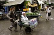 An  elderly Afghan man is carried on a push cart at a market in Kabul, Afghanistan. Insurgents have committed war crimes by attacking ordinary Afghans and killed 669 civilians in 2006, the heaviest toll since the Taliban's ouster in 2001, according to a report released Monday.