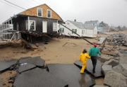 Phil and Dolores Cook walk along what remains of Surf Street in Saco, Maine. A storm Monday wrecked the street and the homes along it.