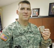 Army Sgt. 1st Class John Fairbanks holds a pacemaker, which was removed during heart transplant surgery in 2005. Fairbanks is back in active duty with the Army Reserves after appealing his ordered retirement.