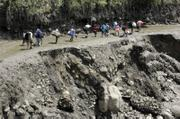 People walk on a  road damaged by the eruption of Nevado del Huila volcado in Bajo Patico, Colombia. The long-dormant volcano erupted late Tuesday and early Wednesday, causing avalanches and floods that swept away houses and bridges and prompted thousands to evacuate.