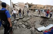 Residents and police inspect a crater caused by a car bomb blast Sunday in Baghdad. Two suicide car bombers attacked a police station in western Baghdad, killing at least 18 people and wounding 82, police said.