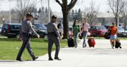 Officers of the Virginia State Police provide security as students return Sunday to the Virginia Tech campus in Blacksburg, Va. Students, from left, Julie Huff, Annie Ellis, and Vanessa Tumminia, carry their belongings into West Ambler Johnston Hall. Students are returning to the campus as classes will resume today.