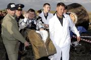 The Russian Space Agency search-and-rescue team officers carry U.S. Space tourist Charles Simonyi  shortly after his landing Saturday in Russian Souyz TMA-9 space capsule about 500 km (310 miles) southwest of the Kazakh town of Karaganda. A Russian cosmonaut and an American astronaut returned to Earth along with a U.S. billionaire whose paid voyage to the international space station ended with a landing on the Kazakh steppe.
