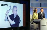 """NBC """"Today"""" television show co-hosts Meredith Vieira and Matt Lauer report Thursday in New York on a video manifesto and photos sent to their network by Virginia Tech gunman  Seung-Hui Cho, shown on a studio monitor at left brandishing a hammer."""
