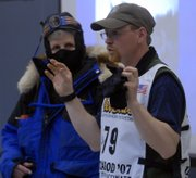 Iditarod competitor Clint Warnke talks about some of the gear he wears in the race as sixth-grade teacher Nancy Dietze, left, tries on the attire for a demonstration.
