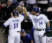 THE ROYALS' ROSS GLOAD, LEFT, celebrates with teammate John Buck after scoring on a single by Alex Gordon. The Royals fell, 9-7, on Tuesday night at Kauffman Stadium.