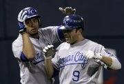 Kansas City's Tony Pena Jr., left, pats teammate David DeJesus (9) on the head after DeJesus hit a two-run home run. DeJesus went 3-for-4 in the Royals' 4-3 victory against the Twins on Wednesday in Minneapolis.