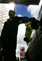 Gas prices loom on a marquis as attendant Shawn Calhoun pumps gas Monday in downtown Portland, Ore. Gasoline prices have gone up more than 8 cents across the country the last two weeks and are up 69 cents so far this year, according to the latest Lundberg Survey released Sunday.