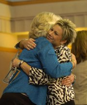 Leadership Lawrence graduate Sara Dawson, right, hugs Mayor Sue Hack after receiving a class plaque. Thirty Lawrence residents graduated from the leadership program on Friday at the Lawrence Chamber of Commerce's Leadership Lawrence Graduation Breakfast at the Kansas Union.
