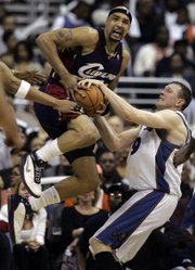Cleveland's Drew Gooden, left, fights for possession with Washington's Darius Songaila. The Cavaliers defeated the Wizards, 98-92, on Saturday in Washington to take a 3-0 lead in their series.