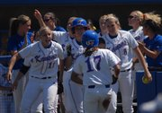 KANSAS UNIVERSITY'S VAL CHAPPLE (17) is greeted by her teammates after scoring the Jayhawks' first run against Oklahoma. KU earned a 2-0 victory Saturday at Arrocha Ballpark.