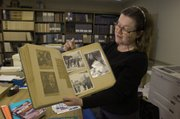 Kansas University Archivist Becky Schulte displays Laird Wilcox's scrapbook of KU during the 1960s. Wilcox's work on Student Union Activities helped bring minority speakers to KU.