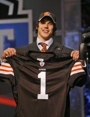 Brady Quinn holds up a Cleveland jersey after being selected 22nd by the Browns. The Dolphins, to the surprise of many, passed on Quinn at No. 9.