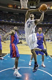 Orlando's Dwight Howard (22) dunks over Detroit's Antonio McDyess, left, and Rasheed Wallace. The Pistons defeated the Magic, 97-93, on Saturday in Orlando, Fla., to sweep their first-round series.