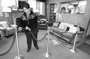 "Volunteer Judy Cantrell secures a velvet rope while cleaning in the former living room of author Laura Ingalls Wilder at the late author&squot;s home in February in Mansfield, Mo. Seventy-five years after the first of Wilder&squot;s ""Little House"" novels was published, the books remain popular internationally."