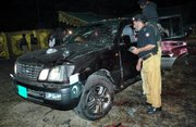 Pakistani police officers examine the damaged vehicle of Pakistan Interior Minister Aftab Khan Sherpao at the site of suicide bombing Saturday in Charsadda, Pakistan. A suicide bomber attempted to kill Pakistan's interior minister in an attack at a political gathering in a northwestern town that left at least 22 dead and 35 wounded, officials said.