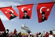 Pro-secular demonstrators walk beneath Turkish flags carrying portraits of Turkey's founder Ataturk during a rally Sunday in Istanbul, Turkey. Hundreds of thousands of pro-secular Turks flooded central Istanbul to demand the resignation of the government, which they fear is leading Turkey toward Islamic rule.