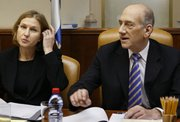 Israeli Foreign Minister Tzipi Livni, left, and Prime Minister Ehud Olmert attend a special meeting of the cabinet in Jerusalem. Livni on Wednesday called on Olmert to resign and said she would challenge him for leadership of the ruling Kadima Party. After the meeting, Olmert remained in control after having secured the backing of a majority of party members.