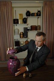 Rumsey-Yost Funeral Home Director Bart Yost displays one of dozens of urns available to house cremated remains on Wednesday at the funeral home located at 601 Indiana.