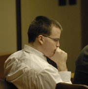 Jason Rose buries his head as a surprise witness testifies that Rose told many people about his plans to burn his residence.  Rose, pictured on Monday at the Lawrence-Douglas County District Court, is charged with killing three people and injuring seven more in the Oct. 7, 2005, fire at Boardwalk Apartments.