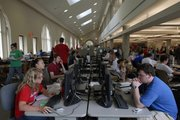 Kansas University students pack into a computer work room in Anschutz Library. Like textbooks, personal computers have become a staple academic item at universities across the country. 